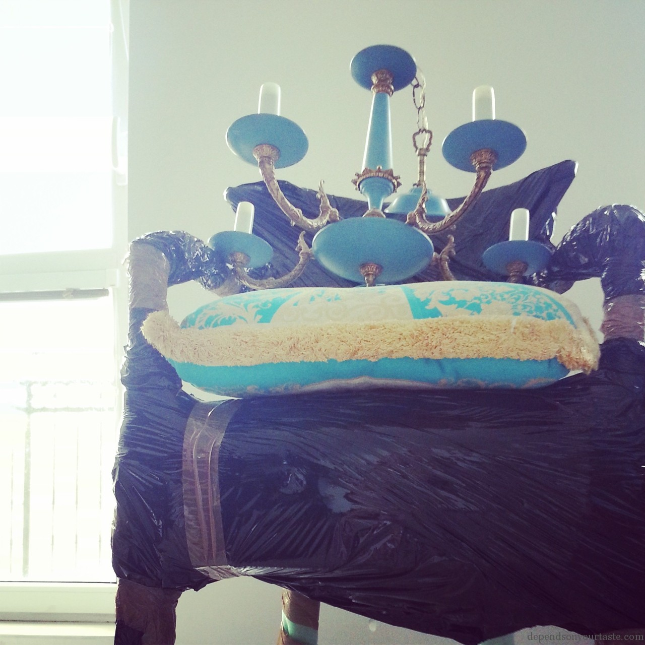 versace cushion ,vintage blue chandelier,black armchair