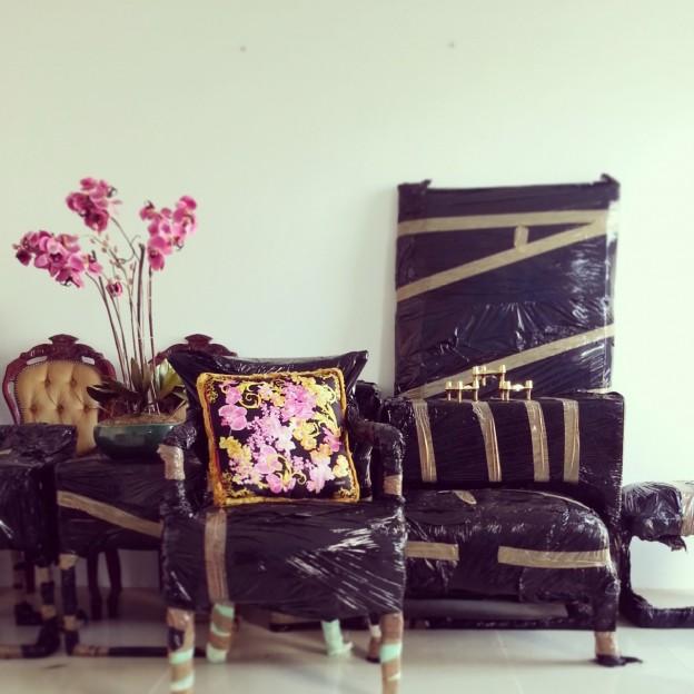 versace cushion ,vintage blue chandelier,black armchair